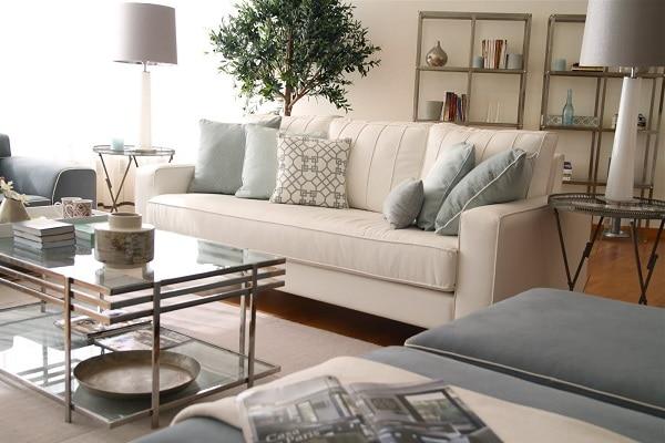 Sofa văng da thiết kế phần đệm không phân chia chỗ ngồi cùng sắc trắng kem tinh khôi tương đồng hòa quyện với màu sơn tường, tủ tài liệu, tủ rượu giúp xóa nhòa ranh giới giữa các vật dụng, nới rộng không gian và tạo sự rộng rãi cho căn phòng