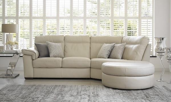 Một chiếc sofa da màu kem trắng có những đường cong nghệ thuật phía bên phải như thế này khi kết hợp với một vài chi tiết bạc, crom và kính của các đồ nội thất khác một cách hợp lý sẽ nâng cao tính thẩm mỹ, làm bừng sáng không gian và tăng thêm sự yên tĩnh, mát mẻ cho căn phòng