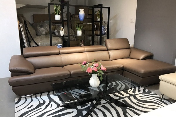 Một cách xử lý hoàn hảo để ngăn cách không gian tiếp khách với khu vực cầu thang phía sau chính là việc sử dụng một bộ sofa góc vuông chữ L màu nâu cà phê và kệ cây trang trí màu đen. Không những thế, bộ sofa có đệm mút inoac Nhật Bản êm ái, da bọc bóng đẹp còn giúp những vị khách cảm thấy thoải mái hơn