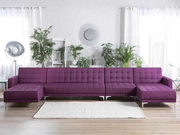Sofa góc vuông chữ U màu tím thiết kế nút bấm trang trí, chân nâng inox sáng bóng mang vẻ đẹp sang trọng, lãng mạn, nổi bật giữa căn phòng màu trắng tinh khôi