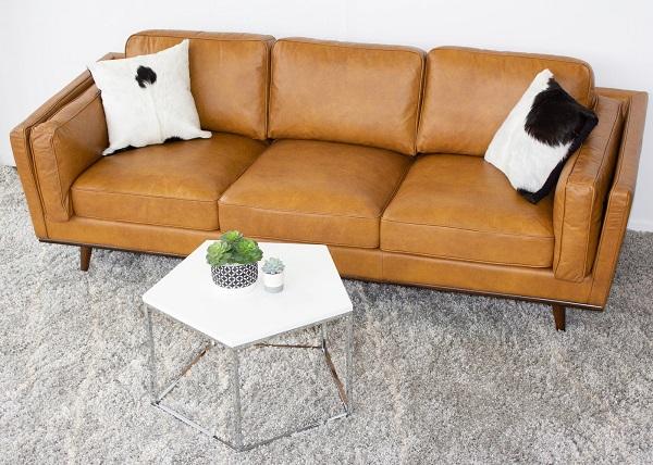 Phối chất liệu màu vàng da bò sáng hơn một chút cùng những chiếc gối tựa trắng – đen tối giản bằng lông mượt mà, chiếc bàn kim loại lục giác màu trắng thanh cảnh, thảm lông xám nền nã, chiếc sofa trông sẽ nổi bật và thu hút hơn