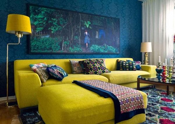 Khi kết hợp với tường màu xanh lam đậm, gối tựa, thảm trải họa tiết nhiều màu với sofa màu vàng cốm, căn phòng trở nên nổi bật, thu hút