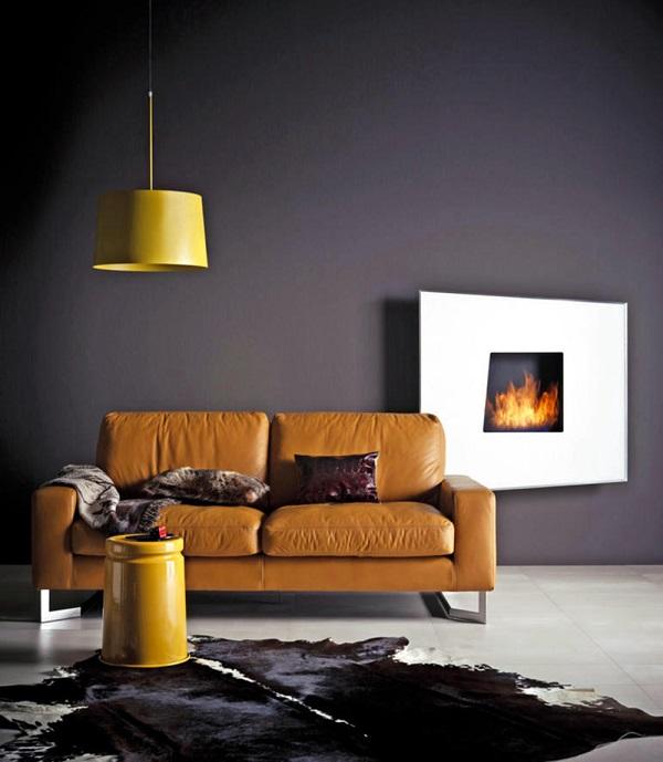 Nếu bạn muốn thể hiện vẻ đẹp cá tính và sự khác biệt thì có thể kết hợp sofa da màu vàng điều thiết kế cơ bản với đèn, bàn kim loại màu vàng, tường sơn màu ghi đậm, sàn lát gạch trắng, trải da trắng – đen và tranh treo tường hình ngọn lửa