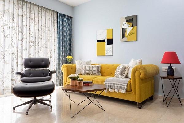 Căn phòng khách nhỏ sẽ trở nên rộng rãi, thu hút hơn với bộ sofa văng màu vàng cỏ úa, tay vịn cong, trang trí nút bấm kết hợp cùng trang treo tường nhấn vàng cỏ úa giữa tông nền sáng của tường, trần, sàn
