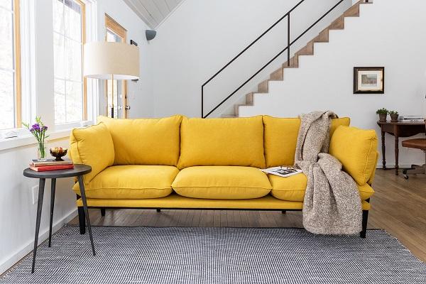 Bộ sofa văng giống như tập hợp của nhiều chiếc gối vải ghép lại đem lại cảm giác êm ái, thoải mái tối đa cho người dùng. Sắc vàng của vải bọc làm cho bộ sofa càng nổi bật rực rỡ, mang tới sự tươi vui cho căn phòng