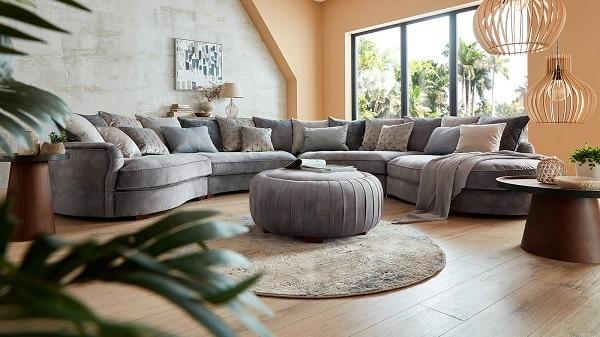 Mẫu sofa góc tròn này gây ấn tượng với người nhìn bởi gối tựa vải ánh bạc phát ra thứ ánh sáng lấp lánh và những đường xếp ly tinh tế, được cắt, khâu tỉ mỉ bằng tay chạy góc mép trong phần lưng. Kết hợp với đó là lớp vải nhung màu xám êm mịn, nhã nhặn mang lại vẻ đẹp sang trọng và sự thoải mái, dễ chịu