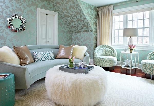 Sự hòa hợp giữa sofa góc tròn bằng vải màu xanh pastel, giấy dán tường hoa văn cùng màu; bàn kim loại và họa tiết trên ghế đôn màu xanh cổ vịt; gối tựa, bàn lông trắng mượt, mềm mại mang đến vẻ đẹp nhẹ nhàng, cảm giác yên bình, thư thái, dễ chịu cho chủ nhân căn phòng