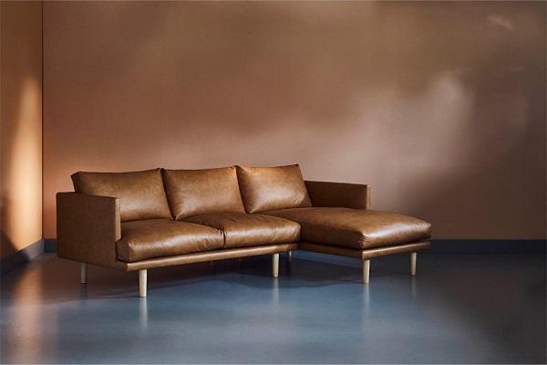 Chân gỗ tiện tròn nâng cao tạo dáng đứng thanh cảnh, nâng tầm đẳng cấp cho sofa góc da màu nâu đồng trong phòng khách nhỏ, giúp tạo vẻ đẹp riêng cho vị trí góc