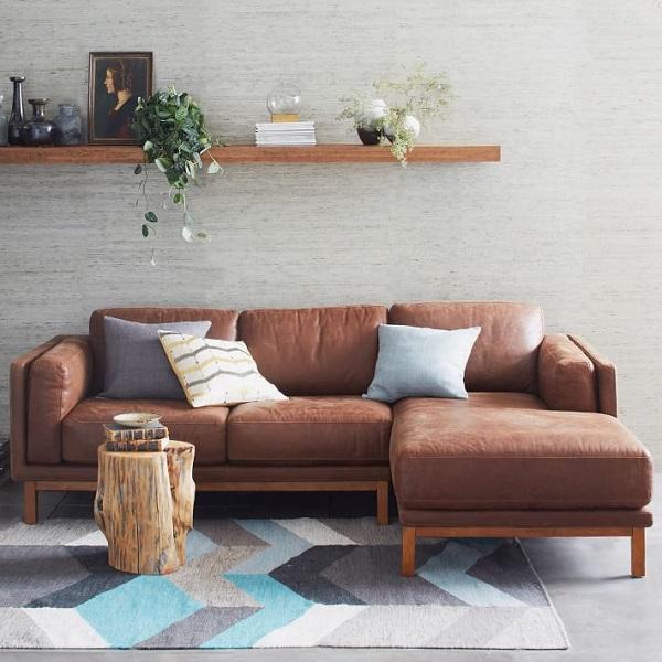 Để tăng sự tươi mới mà vẫn đảm bảo sự hài hòa và thân thiện cho sofa góc da nâu nơi phòng khách nhỏ, bạn có thể trang trí thêm một vài chiếc gối vải màu sắc trang nhã như thế này