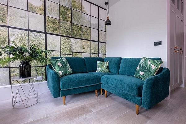 Để mang tới không khí thiên nhiên hòa vào phòng khách nhỏ, hãy chọn một chiếc ghế sofa góc V xanh cổ vịt có chân bằng gỗ kết hợp gối trang trí họa tiết lá cây