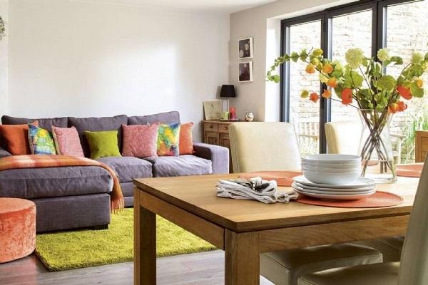 Nhờ sử dụng sofa góc L màu xám trung tính, điểm thêm những chiếc gối màu sắc, đồ nội thất màu sáng cùng cách sắp xếp khoa học, căn phòng khách nhỏ trông tươi sáng và tỏa ra đầy năng lượng tích cực