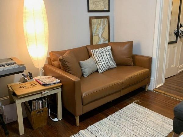 """Kết hợp sofa văng da và các sản phẩm nội thất khác: đèn ngủ, bàn cà phê giúp bạn tạo ra một không gian nghỉ ngơi cực """"chill""""."""