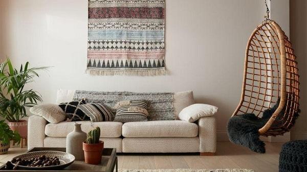"""Không cần phải sử dụng nhiều chi tiết cầu kì, kiểu sofa văng bọc vải nỉ thiết kế đơn giản kết hợp những chiếc gối họa tiết thổ cẩm đặc trưng sẽ mang đến """"làn gió mới"""" cho không gian sống của bạn."""