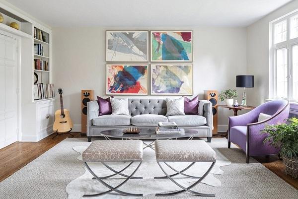 Phòng khách trở nên sang trọng và ấn tượng hơn khi sử dụng sofa văng 3 chỗ chất liệu nỉ nhung màu ghi xám mix cùng ghế đơn và gối tựa sắc tím đầy tinh tế.