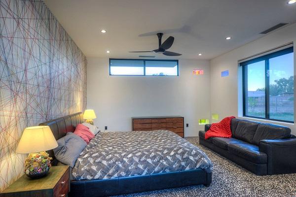 Một chiếc sofa văng da phòng ngủ màu đen sang trọng kê cạnh cửa sổ sẽ tạo ra sự kết nối hoàn hảo với chiếc giường bọc da cùng màu và tăng thêm tính tiện ích cho người dùng