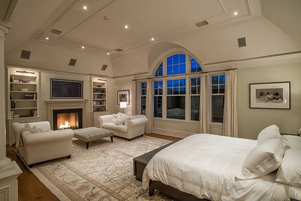 """Bày một đôi ghế sofa da màu trắng tinh khôi kết hợp bàn da xám nhạt nền nã nơi góc phòng, cạnh bếp lò """"ảo"""" tạo ra góc tiếp khách đẹp tuyệt giữa căn phòng ngủ phong cách Bắc Âu"""
