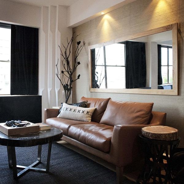 Kê sofa văng da màu nâu sát tường kết hợp với một chiếc bàn có mặt giả gỗ bên cạnh sẽ tạo ra góc ngồi thiên nhiên hoàn hảo cho phòng ngủ