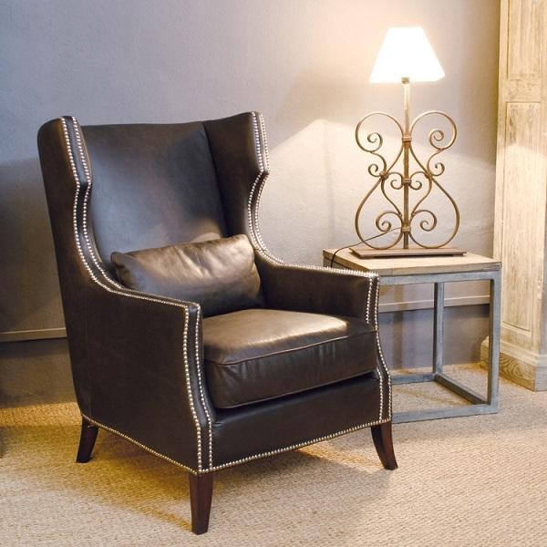 Chân ghế tỉa cong tạo sự vững chãi, lưng ghế uốn cong, ôm lấy lưng người ngồi. Đây là mẫu sofa da phòng ngủ lý tưởng để gia chủ ngồi nghỉ ngơi, suy tư, ôn lại những kỷ niệm xưa cũ khi kết hợp với một chiếc đèn bàn cổ điển, cách điệu như thế này